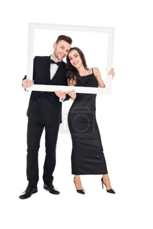 happy elegant couple in black clothes posing with frame, isolated on white