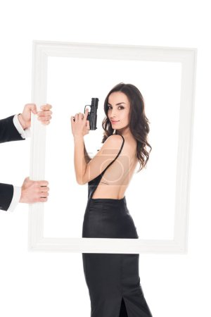 man holding frame in front of beautiful woman with gun, isolated on white