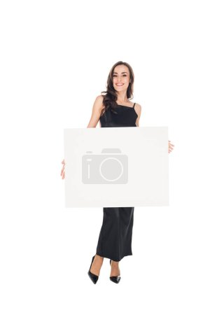 smiling elegant woman in black dress posing with empty board isolated on white