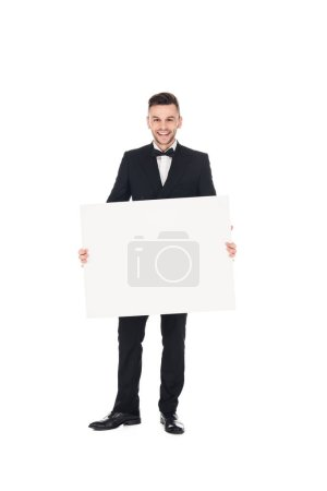 handsome smiling elegant man in black suit posing with empty board isolated on white