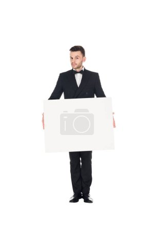 handsome elegant man in black suit posing with blank placard isolated on white