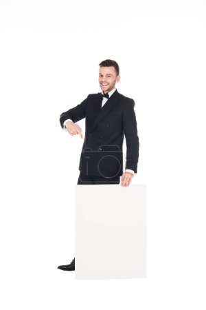 cheerful elegant man in black suit pointing at empty board isolated on white