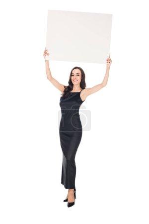 Photo pour Belle femme souriante dans une robe noire posant avec plaque vierge isolé sur blanc - image libre de droit