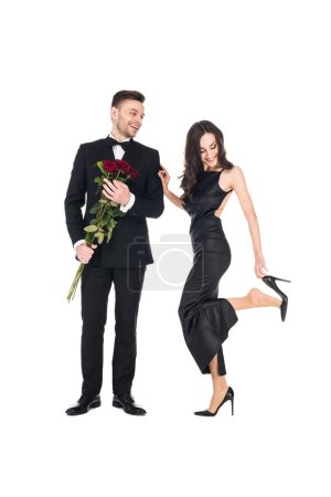 beautiful couple in black clothes posing with red roses on valentines day, isolated on white
