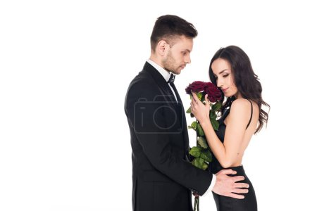 tender couple in black clothes posing with red roses on valentines day, isolated on white