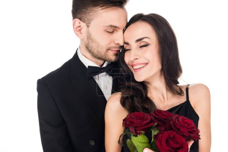 happy cheerful couple in black clothes posing with red roses on valentines day, isolated on white