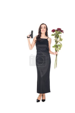 happy elegant secret agent in black dress holding gun and red roses, isolated on white