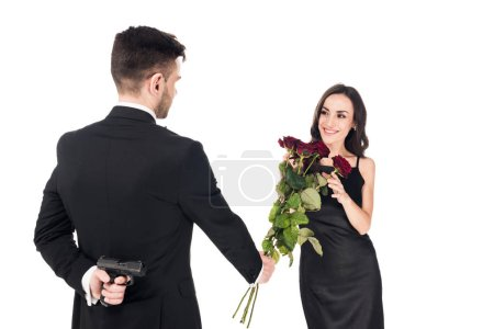 man gifting red flowers to girlfriend while hiding gun behind the back, isolated on white