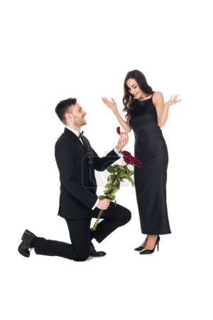 happy man with red roses giving proposal ring in box to excited girl, isolated on white