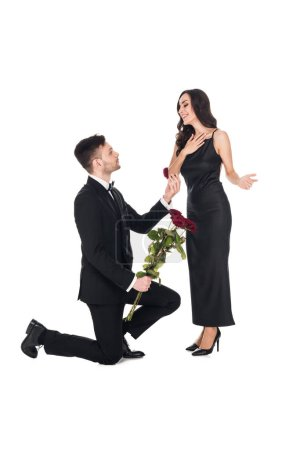 handsome boyfriend with flowers giving proposal ring in box to surprised girlfriend, isolated on white