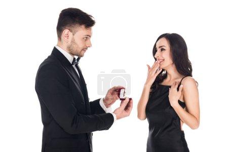 Photo pour Heureux petit ami donnant bague de demande en boîte à petite amie surprise, isolé sur blanc - image libre de droit
