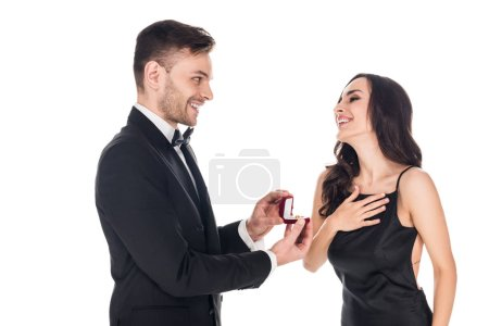 handsome boyfriend giving proposal ring in box to excited girlfriend, isolated on white