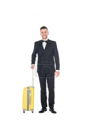 smiling elegant man in black tuxedo posing with travel bag isolated on white