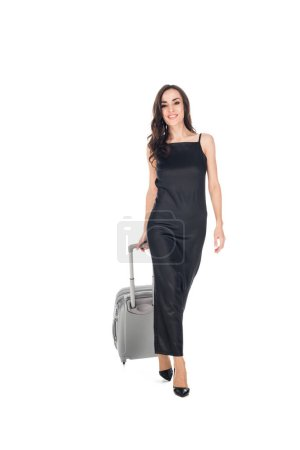 cheerful elegant woman in black dress walking with travel bag isolated on white
