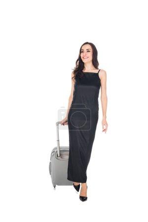 happy elegant female traveler in black dress walking with suitcase isolated on white