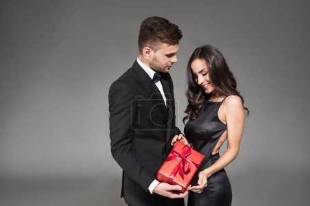 Photo for Beautiful couple in black clothes posing with red gift box on valentines day, isolated on grey - Royalty Free Image