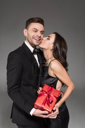 happy woman kissing handsome boyfriend and holding gift box on valentines day, isolated on grey