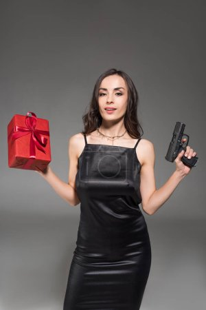 beautiful brunette woman in black dress holding red gift box and gun isolated on grey
