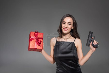 attractive smiling woman holding red gift box and gun isolated on grey