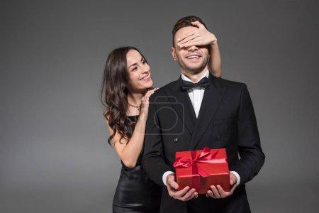 Photo pour Belle femme fermant les yeux et faisant la surprise au petit ami avec présent sur la Saint Valentin, isolé sur gris - image libre de droit