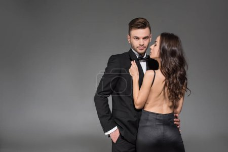 beautiful elegant couple in black clothes hugging isolated on grey