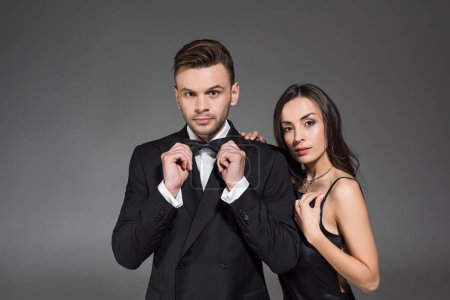 beautiful elegant couple posing in black clothes isolated on grey