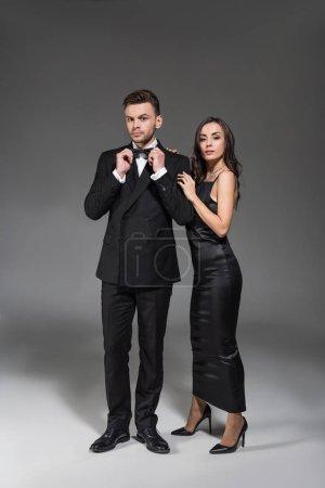 Photo pour Belle amie élégante et son copain en vêtements noirs, posant sur fond gris - image libre de droit