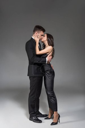 Photo for Beautiful elegant couple kissing and hugging on grey - Royalty Free Image