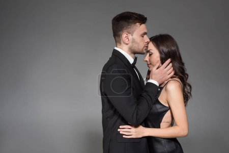 handsome man kissing forehead of beautiful girlfriend isolated on grey