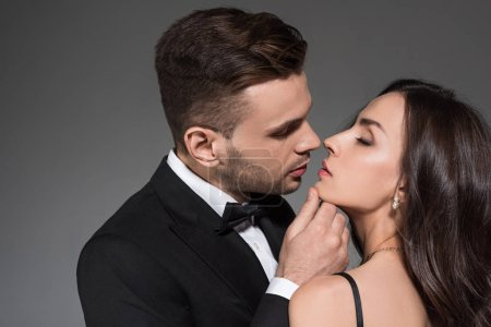 young tender man kissing beautiful girlfriend with closed eyes isolated on grey