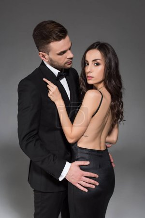 Photo for Elegant couple in black clothes hugging together isolated on grey - Royalty Free Image
