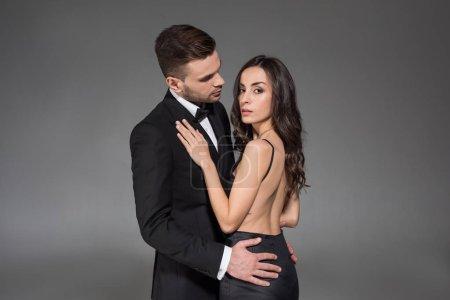 Foto de Atractiva pareja elegante en ropa de color negro que abrazaba aislada en gris - Imagen libre de derechos