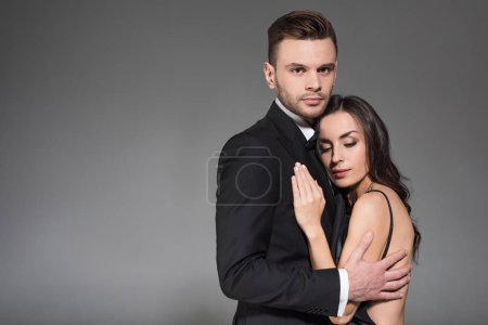 beautiful elegant couple in black clothes hugging together isolated on grey