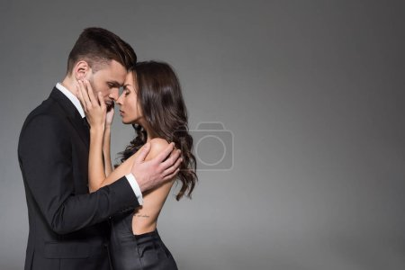 Photo for Tender elegant couple in black clothes hugging with closed eyes isolated on grey - Royalty Free Image