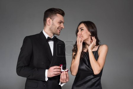 handsome boyfriend holding proposal ring in box for excited girlfriend, isolated on grey