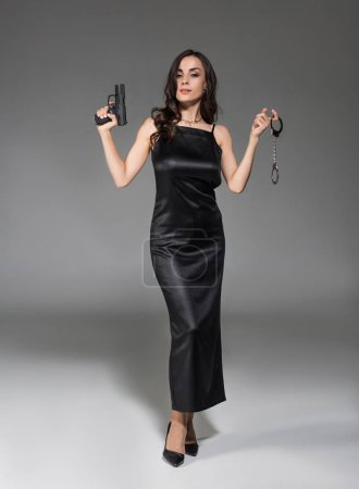 beautiful female secret agent in black dress holding gun and handcuffs on grey