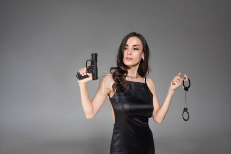 charming brunette secret agent in black dress holding gun and handcuffs, isolated on grey