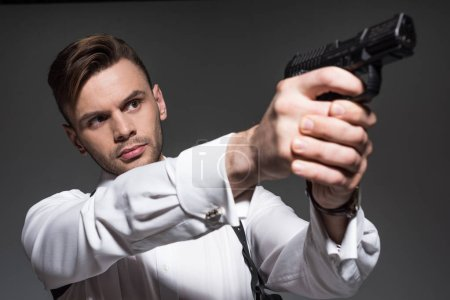 handsome secret agent aiming with handgun isolated on grey