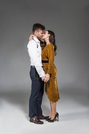 happy beautiful woman in golden dress kissing secret agent with gun on grey