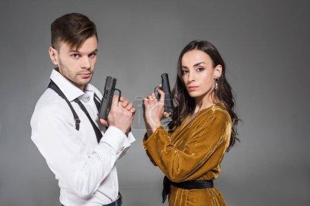elegant confident couple of secret agents posing with handguns, isolated on grey