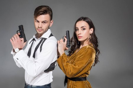 beautiful confident couple of secret agents posing with weapon, isolated on grey