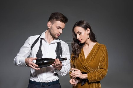 handsome boyfriend pouring champagne for girlfriend isolated on grey