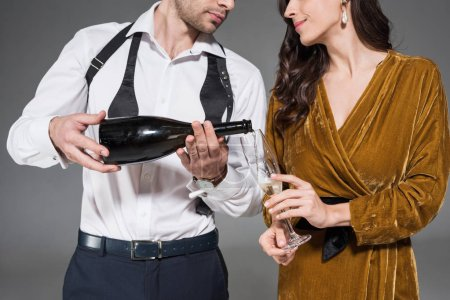 cropped view of boyfriend pouring champagne for girlfriend isolated on grey