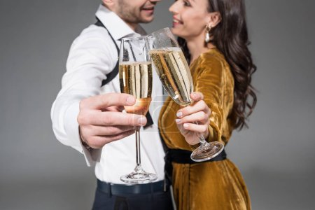 selective focus of couple clinking with champagne glasses isolated on grey
