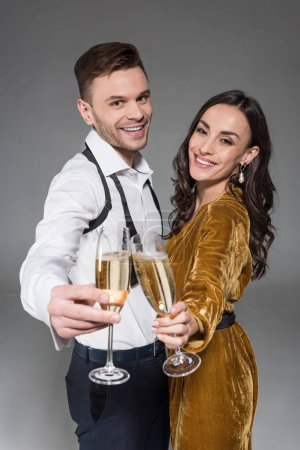 happy couple clinking with champagne glasses isolated on grey