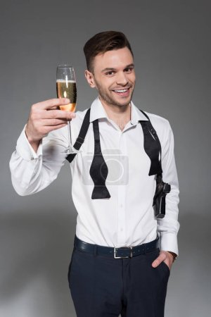 smiling young man toasting with glass of champagne isolated on grey