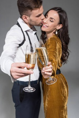 selective focus of kissing couple clinking with champagne glasses isolated on grey
