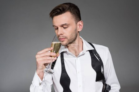 handsome young man drinking champagne isolated on grey