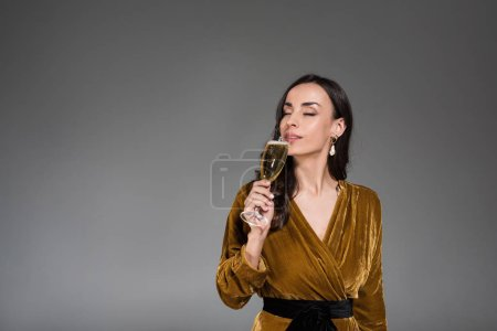 beautiful dreamy woman drinking champagne with closed eyes isolated on grey