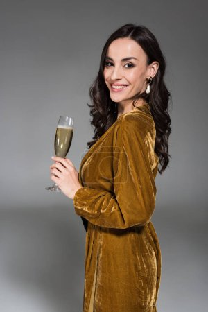 beautiful smiling woman in golden dress holding glass of champagne isolated on grey